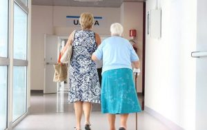elderly woman being escorted through hospital