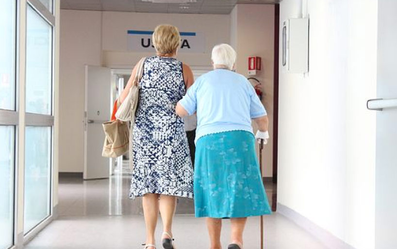 elderly woman being escorted through hospital